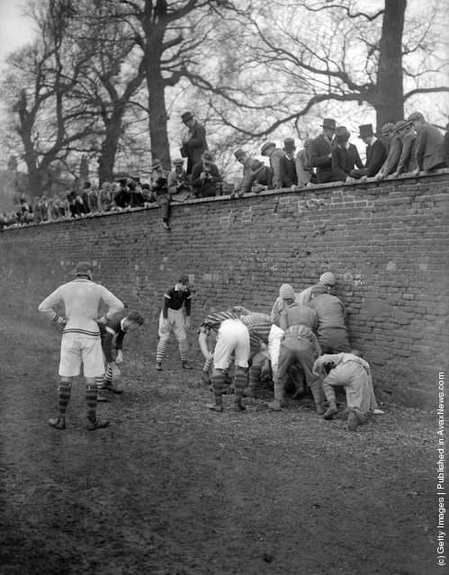 1928: A group of public school boys watch their classmates playing the Eton Wall Game, traditionally played between town and school on St Andrew's Day, and unique to Eton