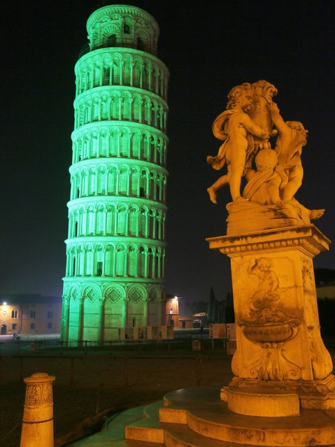 The leaning tower of Pisa is colored in green to celebrate Ireland's national holiday on the eve of the St Patricks Day. (Photo by Fabio Muzzi/AFP Photo)