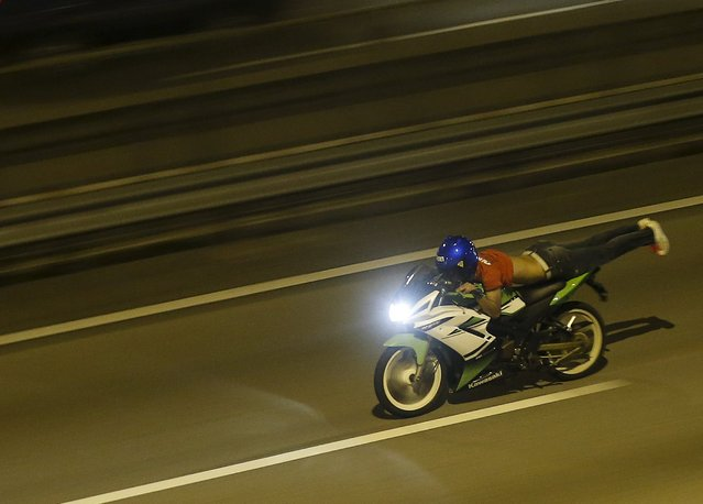 "A motorcyclist performs the superman stunt on a highway in Kuala Lumpur, Malaysia, September 14, 2014. Crowds of small motorbikes ridden by racers – or ""Mat Rempit"", as they are known in Malaysian slang – face off in impromptu races in the Malaysian capital after dark. The decades-old culture is widely frowned upon by largely conservative Malaysians, who fear its potential to encourage gambling, drug abuse, snatch thefts and sexual promiscuity. (Photo by Olivia Harris/Reuters)"