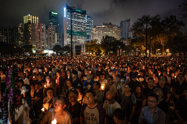 People hold candles as they take part in a candlelight vigil at Victoria Park on June 4, 2019 in Hong Kong, China. As many as 180,000 people are expected to attend a candlelight vigil in Hong Kong on Tuesday during the 30th anniversary of the Tiananmen Square massacre as commemorations took place in cities around the world on June 4 to remember those who died when Chinese troops cracked down on pro-democracy protesters. Thirty years ago, the People's Liberation Army opened fire and killed from hundreds to thousands of protesters in Beijing after hundreds of thousands of students and workers gathered in Tiananmen Square for weeks to call for greater political freedom. No-one knows for sure how many people were killed as China continues to censor any coverage or discussion of the event that takes place during the anniversary. (Photo by Anthony Kwan/Getty Images)