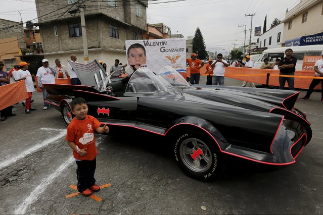 A child poses for a photograph in front of a Batmobile replica, used to promote Valentin Gonzalez, mayoral candidate for the Citizen's Movement Party (Movimiento Ciudadano), in Nezahualcoyotl, on the outskirts of Mexico City, May 22, 2015. Gonzalez vows to fight crime and insecurity by campaigning with a Batmobile replica, in an area where 1 million people live, a growing market for narcotics and illegal goods, local media reported. (Photo by Henry Romero/Reuters)