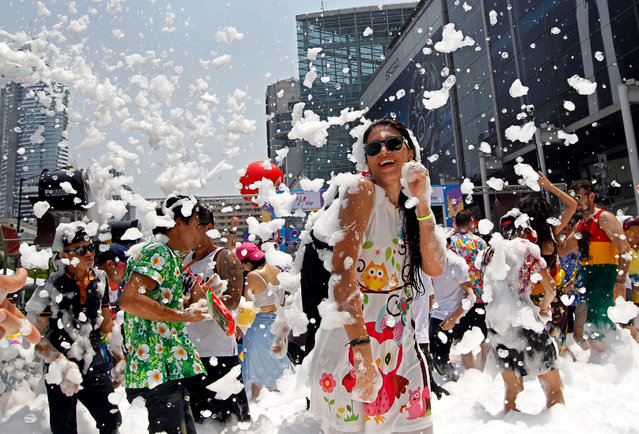 Foreign and Thai revelers dances amid foams during a foam party as part of the annual Songkran celebration, the Thai traditional New Year also known as the water festival in Bangkok, Thailand, 14 April 2016. The three-day Songkran Festival starts on 13-15 April annually and is celebrated with splashing water and putting powder on each others faces as a symbolic sign of cleansing and washing away the sins from the old year. (Photo by Rungroj Yongrit/EPA)
