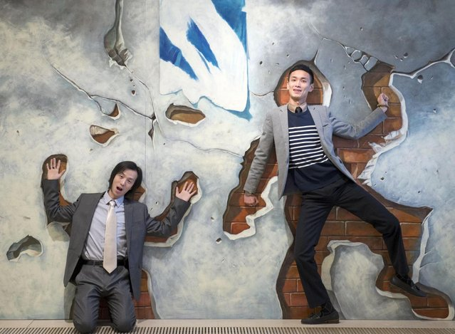 """Artist  Zhang Xu , left, and artist and producer Hesheng Tai, right, both of China, pose in a installation created in a special 3D-technique during a press preview in the exhibition """"You Are The Art""""  by a Chinese artist group at Augustusburg castle in Augustusburg, Germany, Friday, March 21, 2014. (Photo by Jens Meyer/AP Photo)"""