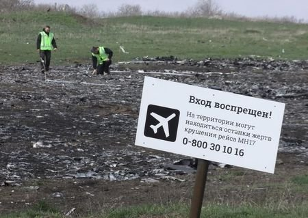 """Investigators work near a sign reading """"No entrance! There may be remains of the victims of flight MH17 crash at the territory"""" at the site of the Malaysia Airlines Boeing 777 plane crash near the village of Hrabove (Grabovo) in Donetsk region, April 16, 2015. REUTERS/Igor Tkachenko"""