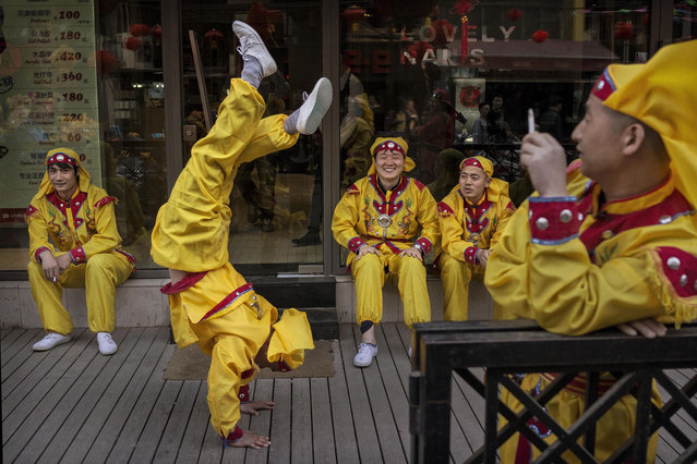 A Chinese dragon dancer does a handstand as he and other performers take a break while shooting a film in the Sanlitun area on April 3, 2014 in Beijing, China. The popular traditional dance is often performed during the annual Spring Festival at Chinese New Year. (Photo by Kevin Frayer/Getty Images)