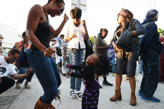 People dance in the street to the of Prince, at Leimert Park in Los Angeles, California where fans gathered to celebrate and remember the pop music icon's life, April 21, 2016. Emergency personnel tried and failed to revive music legend Prince, who died April 21, 2016, at age 57, after finding him slumped unresponsive in an elevator at his Paisley Park studios in Minnesota, the local sheriff said. (Photo by Robyn Beck/AFP Photo)