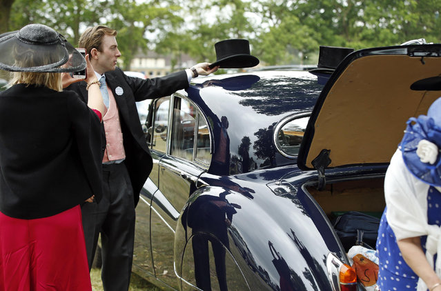 William Beddall places his top hat on the roof of a car as he prepares to pose for photo taken by Milly Beddall as they arrive for the second day of  Royal Ascot horse racing meet at Ascot, England, Wednesday, June 17, 2015. Royal Ascot is the annual five day horse race meeting that Britain's Queen Elizabeth II attends every day of the event.(AP Photo/Alastair Grant)