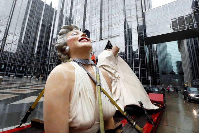 """The tractor trailer carrying Seward Johnson's sculpture """"Forever Marilyn"""" featuring Marilyn Monroe, parks near PPG Plaza during a stopover on Monday, April 7, 2014, in downtown Pittsburgh. The stopover was the tenth and final on the trip from Palm Springs, Calif.,  to New Jersey. (Photo by Keith Srakocic/AP Photo)"""