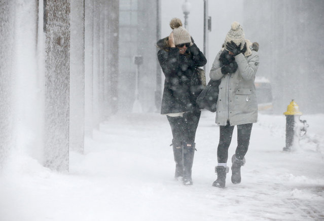 Two women struggle to walk in the blowing snow during a winter storm Tuesday, March 14, 2017, in Boston. (Photo by Michael Dwyer/AP Photo)