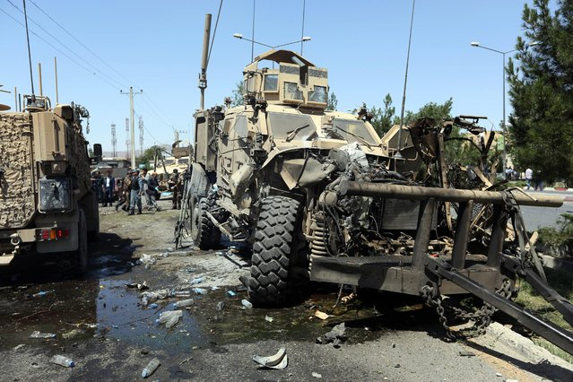 A destroyed armored vehicle remains at the site of a suicide attack on a NATO convoy in Kabul, Afghanistan, Tuesday, June 30, 2015. (Photo by Rahmat Gul/AP Photo)