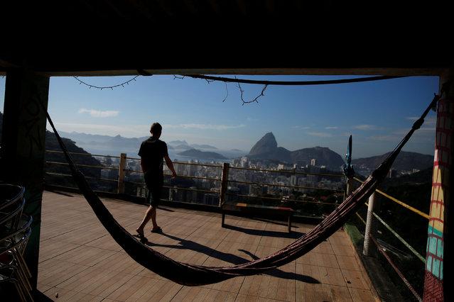 A man walks along a terrace at Pousada Favelinha (Little favela) hostel in Pereira da Silva favela, in Rio de Janeiro, Brazil, April 21, 2016. (Photo by Pilar Olivares/Reuters)