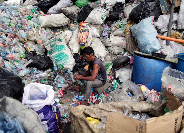 A Filipino informal settler collects recyclable plastic bottles at a slum area in Quezon city, east of Manila, Philippines, 25 February 2019 (issued 13 June 2019). (Photo by Francis R. Malasig/EPA/EFE)