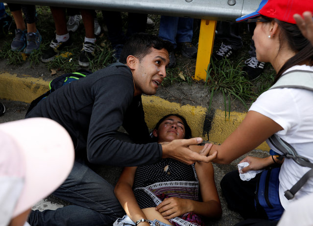 Demonstrators help a fellow protester during clashes with security forces during an opposition rally in Caracas, Venezuela on April 4, 2017. (Photo by Carlos Garcia Rawlins/Reuters)
