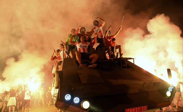 Supporters and players of Red Star Belgrade celebrate with flares on top of an armored troop carrier in Belgrade, Serbia, Tuesday, August 27, 2019. After parking a battle tank at the gates of their stadium, Red Star Belgrade fans and players packed into an open-top armored troop carrier to mark their Champions League qualification. (Photo by AP Photo)