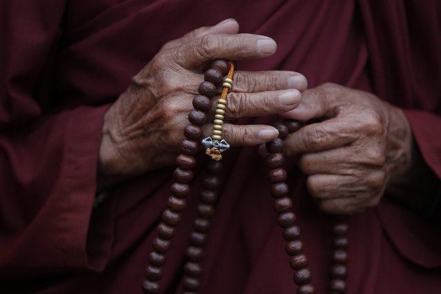 A Tibetan monk offers prayers to mark the 80th birthday of Tibetan spiritual leader, the Dalai Lama, in Kathmandu, Nepal, Monday, July 6, 2015. (Photo by Niranjan Shrestha/AP Photo)