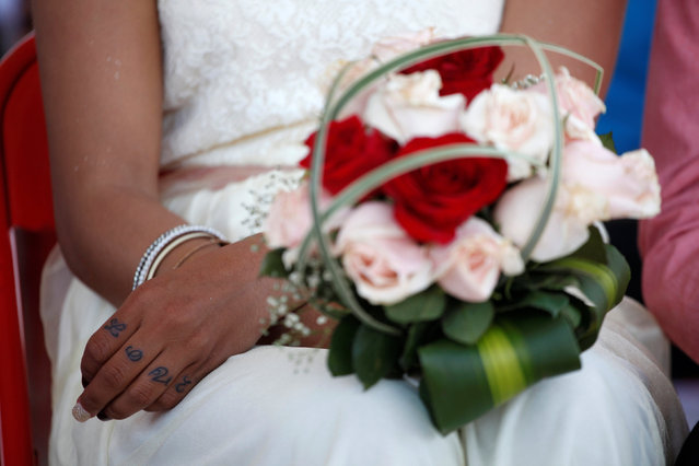 A woman holds a flower bouquet during a mass wedding ceremony at the state prison in Ciudad Juarez, Mexico, May 6, 2016. (Photo by Jose Luis Gonzalez/Reuters)