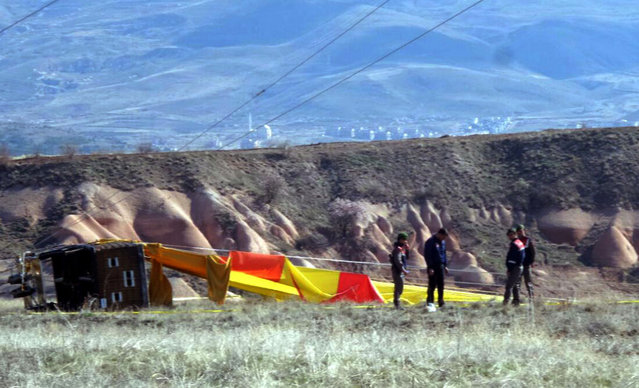 Security members investigate at the site after a hot air balloon hit a high-voltage transmission line and crashed near Cappadocia, a popular tourist destination in central Turkey, Sunday, April 9, 2017. The state-run Anadolu Agency says several hot air balloons lifted off Sunday in Turkey's Cappadocia region to give tourists a scenic view of the historic site, and one hit the electric line during its descent. (Photo by DHA-Depo Photo via AP Photo)