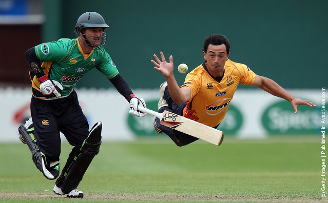 Ronald Karatiana of the Firebirds fields the ball off his own bowling while Kruger van Wyk of the Stags attempts to make his ground during the HRV Cup Twenty20 match between the Wellington Firebirds and Central Stags at Basin Reserve