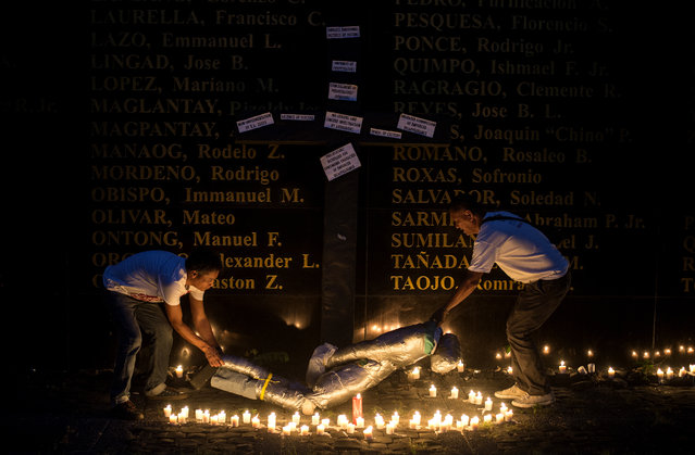People lift a mock victim during a prayer vigil in support of the families of victims of extra-judicial killings in Manila on April 12, 2017. More than 6,000 people have died, seven months after President Rodrigo Duterte ordered an unprecedented crime war on drugs that has drawn global criticism but enjoys popularity in the mainly Catholic nation. (Photo by Noel Celis/AFP Photo)