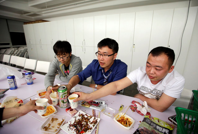 Han Liqun (C), a HR manager of RenRen Credit Management Co., drinks with his colleagues Kou Meng (L) and Ma Zhenguo after finishing work, after midnight, in Beijing, China, April 27, 2016. Office workers sleeping on the job is a common sight in China, where a surplus of cheap labour can lead to downtime at work. But in China's technology sector, where business is growing faster than many start-up firms can hire new staff, workers burn the midnight oil to meet deadlines and compete with their rivals. Some companies provide sleeping areas and beds for workers to rest during late nights. (Photo by Jason Lee/Reuters)