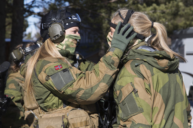 A soldier helps another with her ear protection at the Terningmoen Camp in Elverum, Norway on March 23, 2017. Capt. Ole Vidar, the officer leading the training program, said that the female unit has shown a stronger sense of solidarity among its members than the men in the elite platoon. (Photo by Carolina Reid/NBC News)