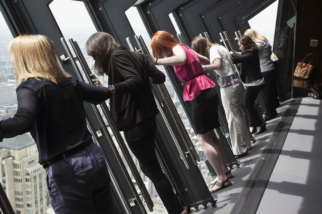 In this Thursday, May 8, 2014 photo, guests look down from the Tilt!, a new tourist attraction that provides guests a unique view of the downtown area from the 94th floor of the John Hancock Building, after it was unveiled in Chicago. People hold onto handrails as the glass and steel facade tilts forward 30 degrees. (Photo by Ashlee Rezin/AP Photo/Sun-Times Media)