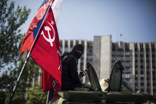 A masked pro Russia man is seen atop an APC flying a Russian flag, top, and a Donetsk People's Republic flag, as it stands in front of the occupied administration building in Donetsk, Ukraine, Saturday, May 10, 2014.  Two restive regions in eastern Ukraine are preparing to vote on declaring sovereignty and ceding from Ukraine, in a referendum on Sunday in the Donetsk and Luhansk regions. (Photo by Manu Brabo/AP Photo)