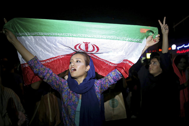 An Iranian woman holds up an Iranian flag as people celebrate a landmark nuclear deal in Tehran, Iran, Tuesday, July 14, 2015. Overcoming decades of hostility, Iran, the United States, and five other world powers struck a historic accord Tuesday to check Tehran's nuclear efforts short of building a bomb. (Photo by Ebrahim Noroozi/AP Photo)