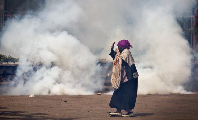 An elderly woman caught up in the clashes holds her hands in the air as a riot policeman approach amidst clouds of tear gas, during a protest in downtown Nairobi, Kenya Monday, May 16, 2016. (Photo by Ben Curtis/AP Photo)