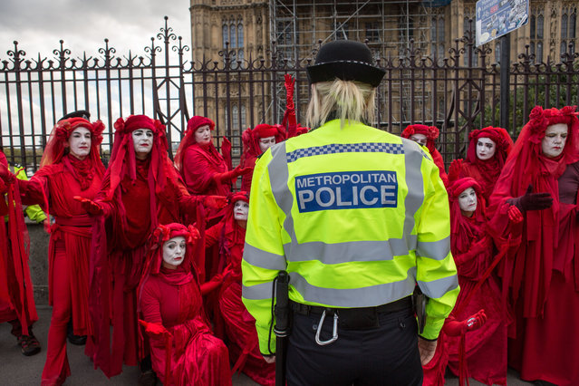 """Environmentalist performance art troupe the """"Red Rebel Brigade"""" perform before a police officer, during the environmental protest by Extinction Rebellion activist group in London, UK on October 8, 2019. Extinction Rebellion is an international movement that uses non-violent civil disobedience in an attempt to halt mass extinction and minimise the risk of social collapse. The group has blocked a number of key junctions in central London. (Photo by Rahman Hassani/SOPA Images/Rex Features/Shutterstock)"""