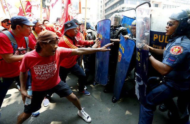 """Protesters clash with riot police as they attempt to force their way closer to the U.S. Embassy to mark the global celebration of May Day in Manila, Philippines Monday, May 1, 2017. As in the past years, workers mark May Day with calls for higher wages and an end to the so-called """"Endo"""" or contractualization. (Photo by Bullit Marquez/AP Photo)"""