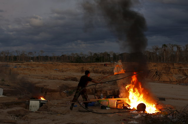 A Peruvian police officer burns equipment used by illegal miners during an operation to destroy illegal gold mining camps in a zone known as Mega 14, in the southern Amazon region of Madre de Dios July 13, 2015. (Photo by Janine Costa/Reuters)