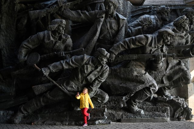 A girl takes a selfie in front of a sculptural composition at the WWII open air museum in Kiev on October 29, 2019. Ukraine marks the 75th anniversary of the country's liberation from the Nazis. (Photo by Sergei Supinsky/AFP Photo)