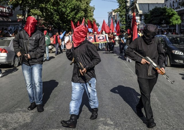 Armed and masked leftist militants demonstrate during the funeral of Monday's explosion victims in Suruc, in Istanbul, Turkey, Tuesday, July 21, 2015. Authorities suspected the Islamic State group was behind an apparent suicide bombing Monday in Suruc in southeastern Turkey that killed tens of  people and wounded nearly 100 – a development that could represent a major expansion by the extremists at a time when the government is stepping up efforts against them. (Photo by Cagdas Erdogan/AP Photo/Depo Photos)