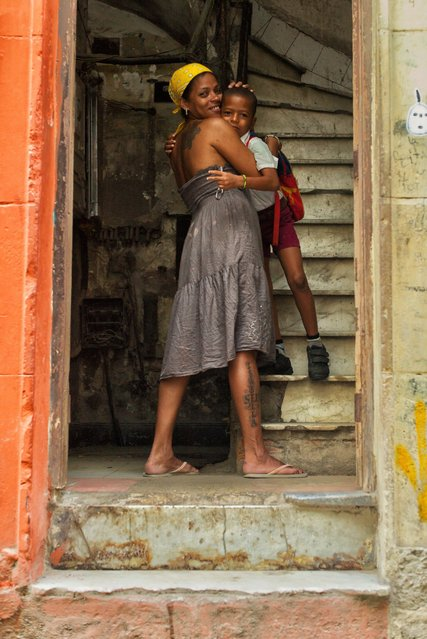 A local mother hugs her son goodbye before he leaves for school in Old Havana, Cuba, May 3, 2016. (Photo by Dotan Saguy)