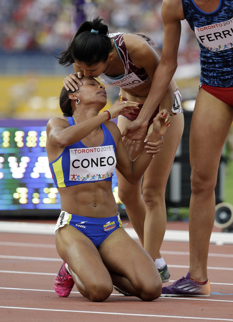 Colombia's Muriel Coneo is congratulated by competitors as she kneels on the ground after winning the gold medal in the finals of the women's 1500 meter run at the Pan Am Games in Toronto, Saturday, July 25, 2015. (Photo by Mark Humphrey/AP Photo)