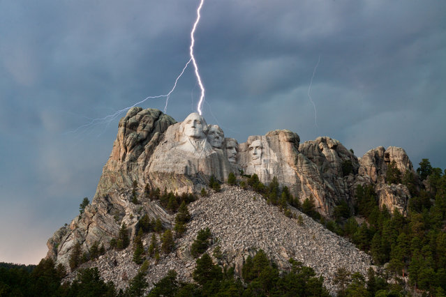 """""""Electric Washington"""". On the 2nd national park visit during a western road trip with my parents, I got to witness a very awe inspiring moment at Mount Rushmore. While diffused front lighting illuminates the faces of the presidents on Mount Rushmore at sunset, a storm rolls in and lightning strikes President Washington, creating a scene that only lasts for 1/50th of a second. Photo location: Mount Rushmore, South Dakota. (Photo and caption by Wray Sinclair/National Geographic Photo Contest)"""