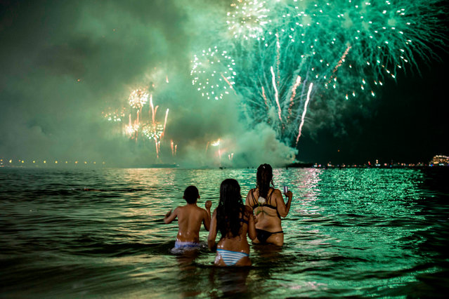 People watch fireworks from the water on Copacabana beach in Rio de Janeiro, Brazil, during the New Year celebration on January 1, 2019. (Photo by Daniel Ramalho/AFP Photo)