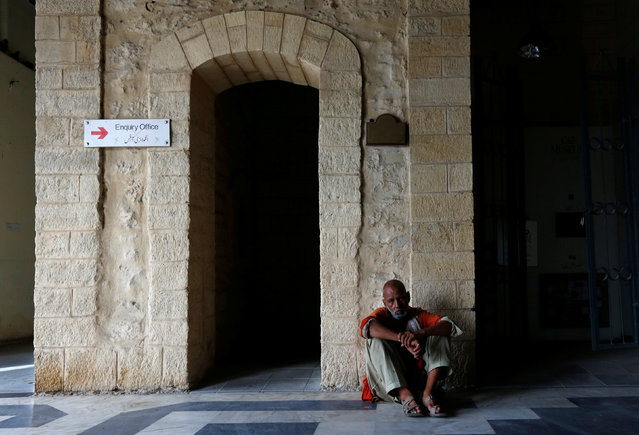 A porter, also known as a coolie, rests on a hot summer day outside inquiry office at railway station in Karachi, Pakistan, May 25, 2016. (Photo by Akhtar Soomro/Reuters)