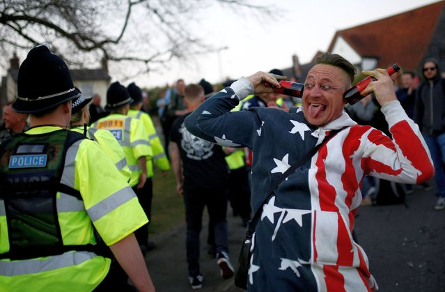 A fan gestures next to a police officer while celebrating the life of British singer Keith Flint of techno group The Prodigy after his funeral in Braintree, Essex, Britain, March 29, 2019. (Photo by Henry Nicholls/Reuters)