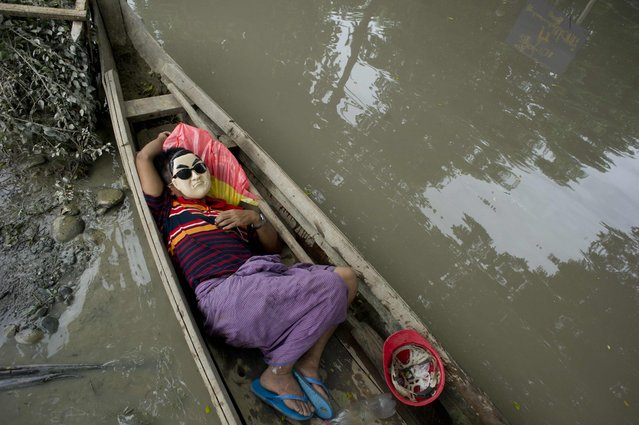 A resident rests in a boat next to floodwaters in Kalay, upper Myanmar's Sagaing region on August 3, 2015. Relentless monsoon rains have triggered flash floods and landslides, destroying thousands of houses, farmland, bridges and roads – with fast-flowing waters hampering relief efforts. (Photo by Ye Aung Thu/AFP Photo)