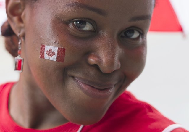 A woman enjoys the festivities during the annual Canada Day parade in Montreal, Tuesday, July 1, 2014. (Photo by Graham Hughes/The Canadian Press)