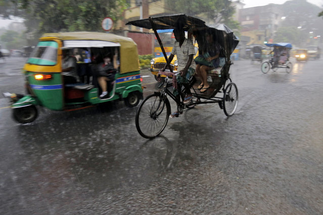 A rickshaw driver transports a passenger in the rain in Kolkata, India, on Jule 2, 2014. Normal traffic was affected in several areas of the city because of overnight rainfall that caused water-logging, according to news reports. (Photo by Bikas Das/Associated Press)