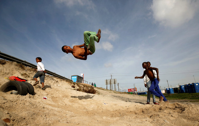 Youths somersault over old tyres in the Khayelitsha township, near Cape Town, South Africa May 25, 2017. (Photo by Mike Hutchings/Reuters)