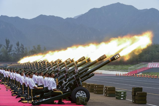 Paramilitary policemen and members of a gun salute team fire cannons during a training session for a military parade to mark the 70th anniversary of the end of the World War Two, at a military base in Beijing, China, August 1, 2015. (Photo by Reuters/Stringer)