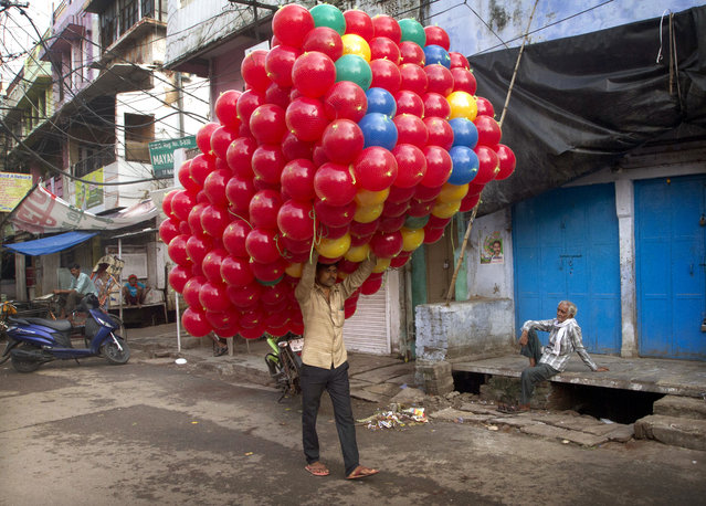 An Indian balloon seller carries loads of balloons, purchased from a whole seller to be sold in a market, in Allahabad, India, Friday, July 14, 2017. Each balloon is purchased $0.15 from wholesale market and is sold for $0.30 to customers. (Photo by Rajesh Kumar Singh/AP Photo)