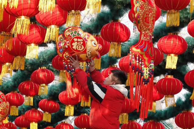 A staff member hangs decoration for a lantern arch at a park ahead of the Chinese Lunar New Year celebrations in Beijing, China on January 19, 2020. (Photo by Reuters/China Daily)