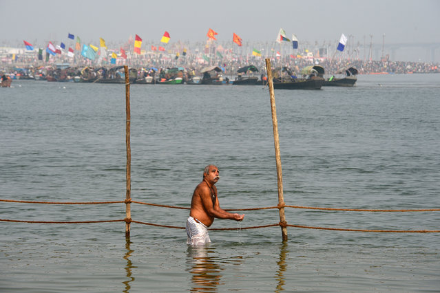 A devotee offers prayers as he takes a holy dip in the Ganges river to observe Paush Purnima festivities, which marks the beginning of the Magha month in the Hindu calendar, during the Magh Mela festival in Allahabad on January 10, 2020. (Photo by Sanjay Kanojia/AFP Photo)