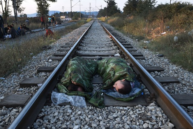 Syrian refugees sleep on railway lines near the train station of Idomeni, northern Greece,  on Wednesday, August 12, 2015. Greece is Europe's main entry point for people arriving by sea, as the alternative route from north Africa to Italy has become increasingly dangerous due to fighting in Libya. From Greece, the migrants move north through the Balkans, hoping to gain asylum, preferably in Germany, the Netherlands or Scandinavia. (Photo by Giannis Papanikos/AP Photo)