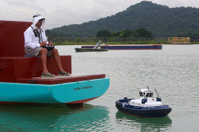 A Panama Canal pilot maneuvers a miniature tugboat as he sits on a scale cargo boat during a training day at the scale model maneuvering training facility of the Panama Canal, a day before the inauguration of the Panama Canal Expansion project on the outskirts of Panama City, in Panama June 25, 2016. (Photo by Alberto Solis/Reuters)